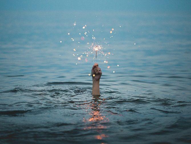 рука с бенгальским огнем в воде